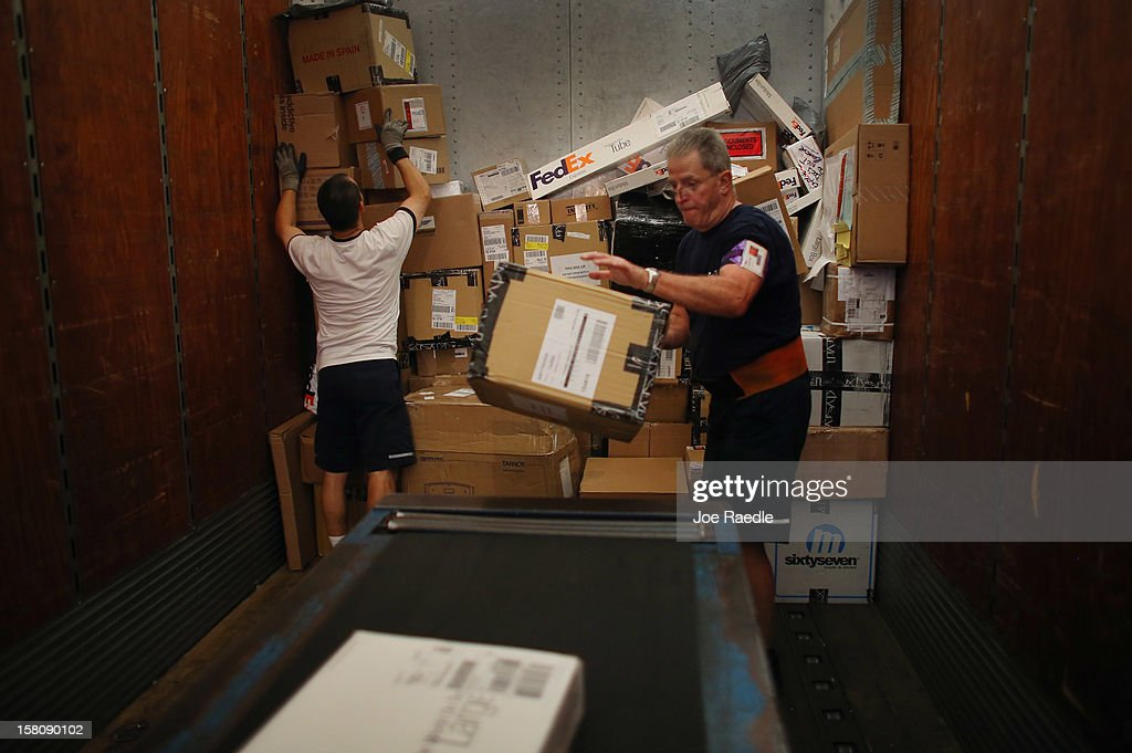 FedEx employees, Jorge Chey (L) and Bill Falbo, sort through items being shipped through the Fedex World Service Center on December 10, 2012 in Doral, Florida. FedEx Corp. expects today to be the busiest shippping day of the year when 19 million packages are expected to move through their system.