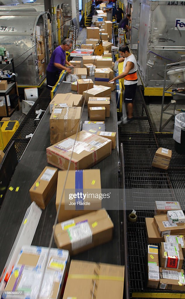 FedEx employees, Rene Carballo (L) and Alexis Barzags, sort through items being shipped through the Fedex World Service Center on December 10, 2012 in Doral, Florida. FedEx Corp. expects today to be the busiest shippping day of the year when 19 million packages are expected to move through their system.