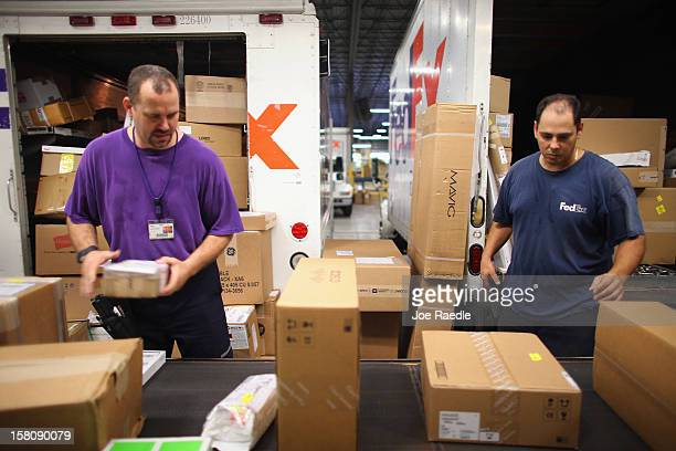 FedEx employees Robin Abner and Ron Shaheen sort through items being shipped through the Fedex World Service Center on December 10 2012 in Doral...