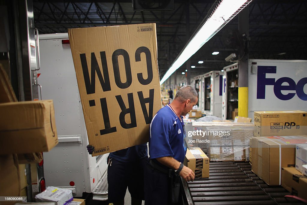 FedEx employees sort through items being shipped through the Fedex World Service Center on December 10, 2012 in Doral, Florida. FedEx Corp. expects today to be the busiest shippping day of the year when 19 million packages are expected to move through their system.