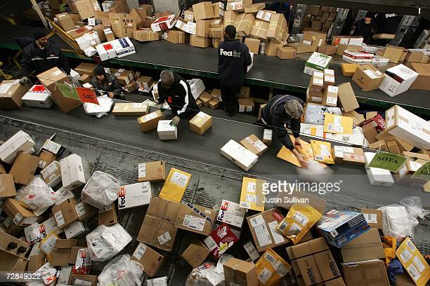FedEx worker sort through a pile of boxes at the FedEx sort facility at the Oakland International Airport December 18 2006 in Oakland California Days...