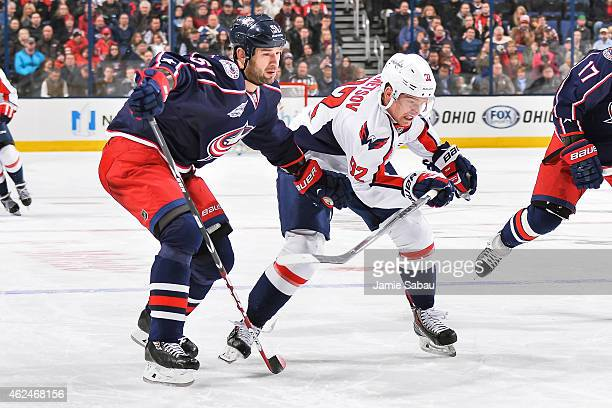 Fedor Tyutin of the Columbus Blue Jackets and Evgeny Kuznetsov of the Washington Capitals chase after a loose puck on January 27 2015 at Nationwide...
