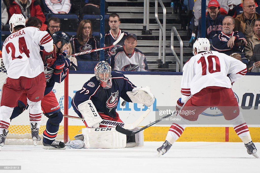 Fedor Tyutin #51 of the Columbus Blue Jackets and Martin Erat #10 of the Phoenix Coyotes watch as goaltender Blue Jackets goalie Sergei Bobrovsky #72 follows a loose puck during the first period on April 8, 2014 at Nationwide Arena in Columbus, Ohio.
