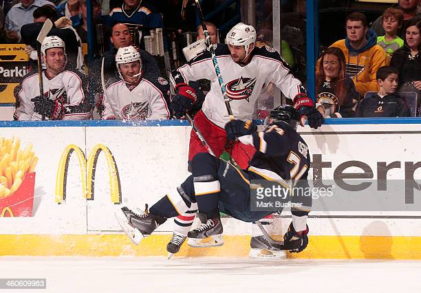 Fedor Tyutin of the Columbus Blue Jackets checks TJ Oshie of the St Louis Blues during an NHL game on January 4 2014 at Scottrade Center in St Louis...