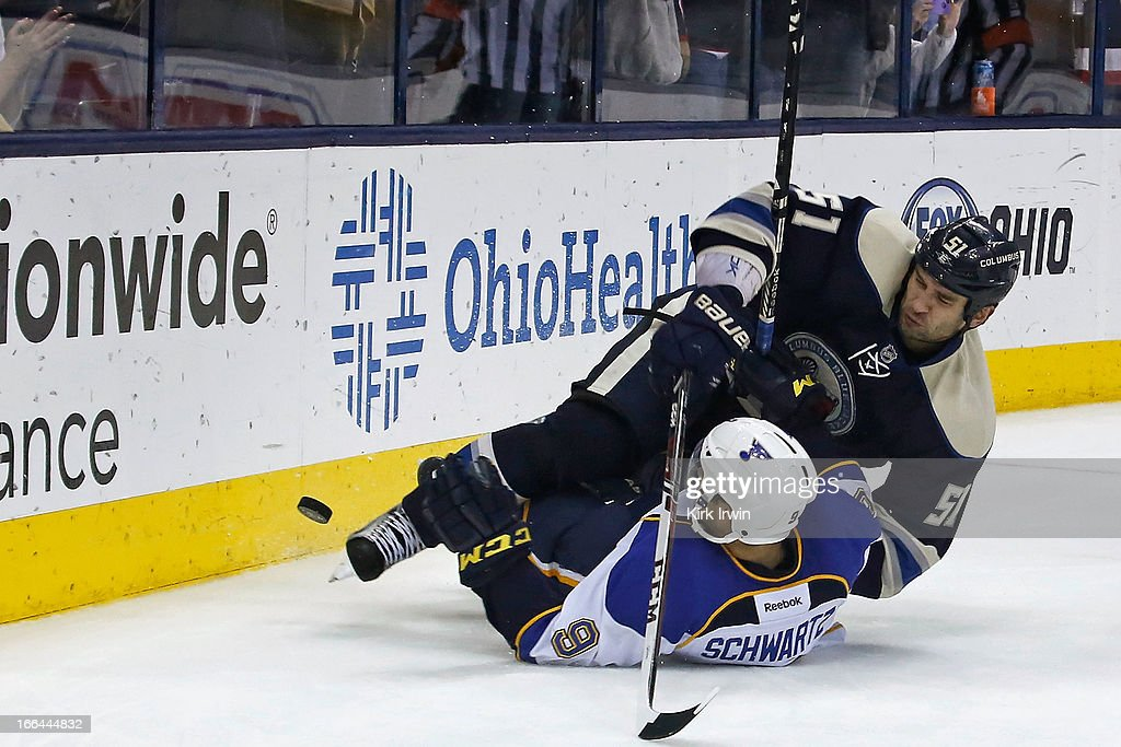 Fedor Tyutin #51 of the Columbus Blue Jackets falls onto Jaden Schwartz #9 of the St. Louis Blues while chasing after a loose puck during the third period on April 12, 2013 at Nationwide Arena in Columbus, Ohio. Columbus defeated St. Louis 4-1.