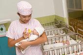 Little nurse feeding newborn with baby bottle