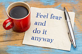 Feel fear and do it anyway - motivational handwriting on a napkin with a cup of coffee