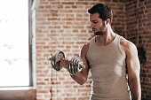 Confident muscled young man wearing sport wear and exercising with dumbbell in loft interior