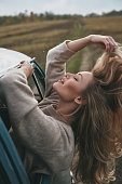 Attractive young smiling woman leaning out the van?s window and keeping hand in hair while enjoying the car travel