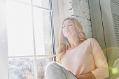 Attractive young woman keeping eyes closed and smiling while sitting on the window sill at home