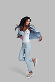 Full length studio shot of attractive young woman in casual wear smiling while jumping against grey background