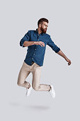 Full length of handsome young man looking away while jumping against grey background