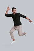 Full length of playful young man gesturing and smiling while jumping against grey background