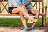Close-up of loving couple bonding to each other while sitting on the bench in park
