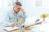 Frustrated mature man looking exhausted while sitting at his working place and carrying his glasses in hand