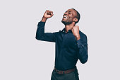 Happy young African man gesturing and keeping eyes closed while standing against grey background