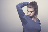 sad woman looking at sweat mark on her blouse, lifestyle concept. photo taken in studio.