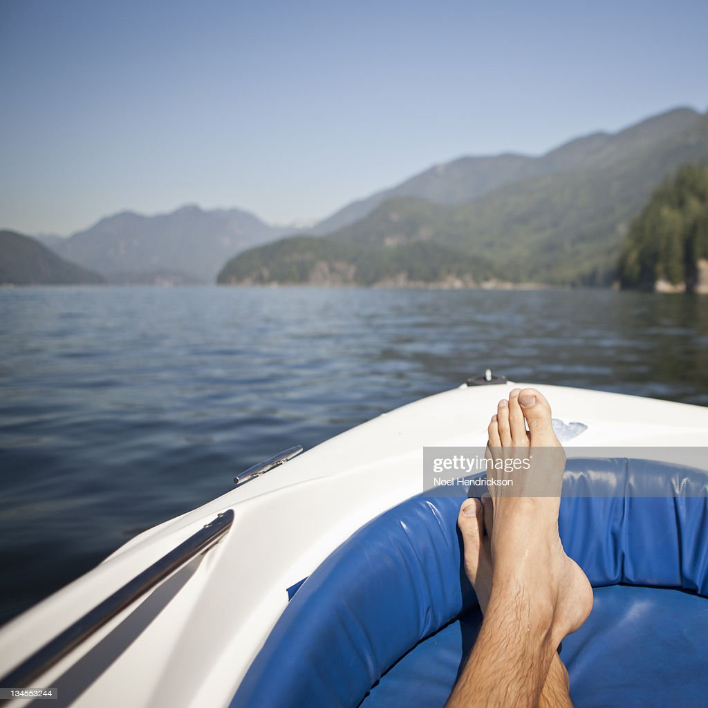 Feet crossed on the back of an anchored boat : Stock Photo