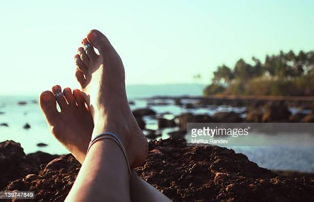 Feet crossed overlooking shore