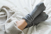 Pair of feet in gray socks on a bed under a cozy blanket.