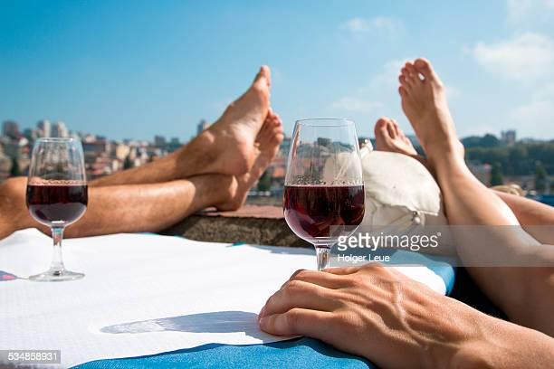 Feet, hand and red wine glasses in old town