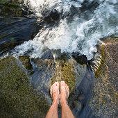 feet of male standing in waterfall