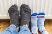 Feet in woolen winter socks warm their feet and relaxing near heating radiator at home.