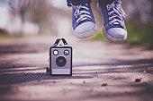 Feet jumping next to old box camera
