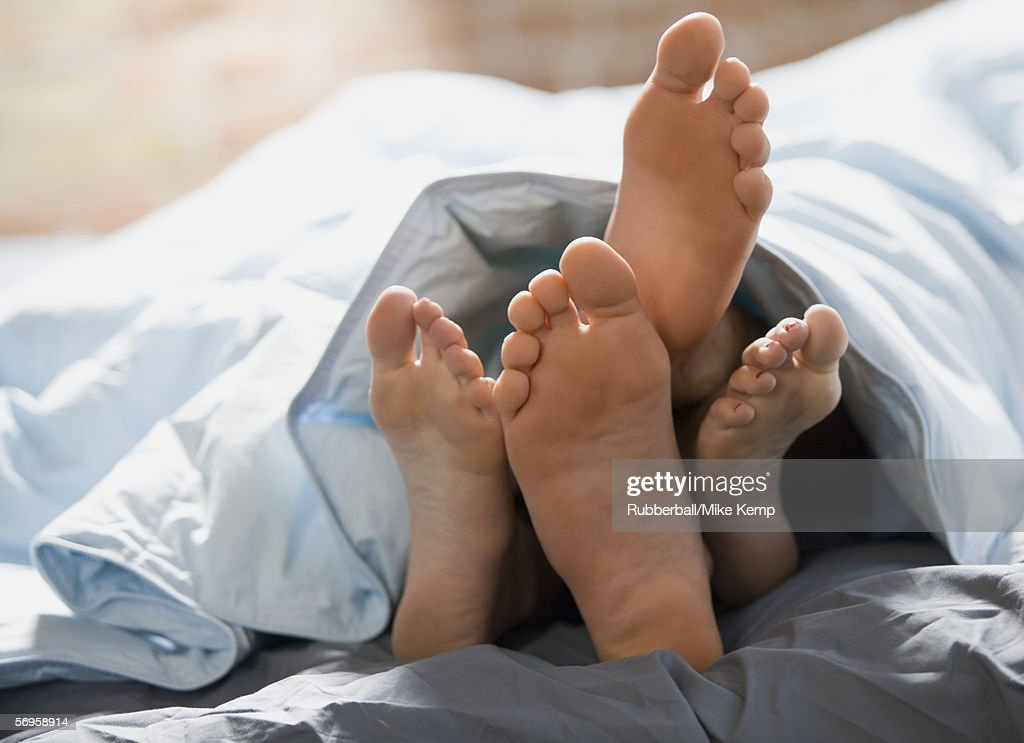 Feet of a couple lying on the bed : Stock Photo