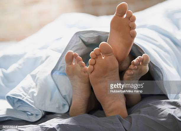 Feet of a couple lying on the bed