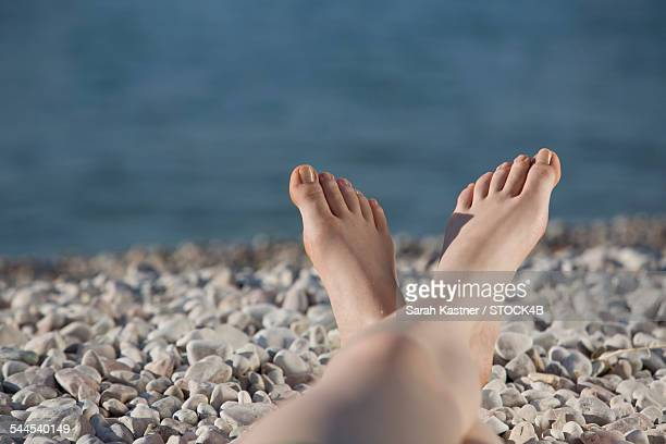 Feet of a woman lying on pebble beach, Lake Garda, Italy