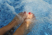 Feet of a woman relaxing in a Jacuzzi.