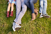 Feet of a young family lying on grass in a park, crop shot