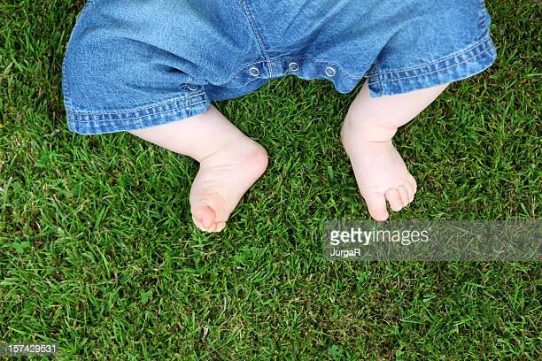 Feet of Baby in Jeans Lying Down On Grass in Summer