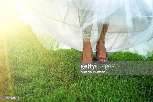 Feet of bride walking on grass