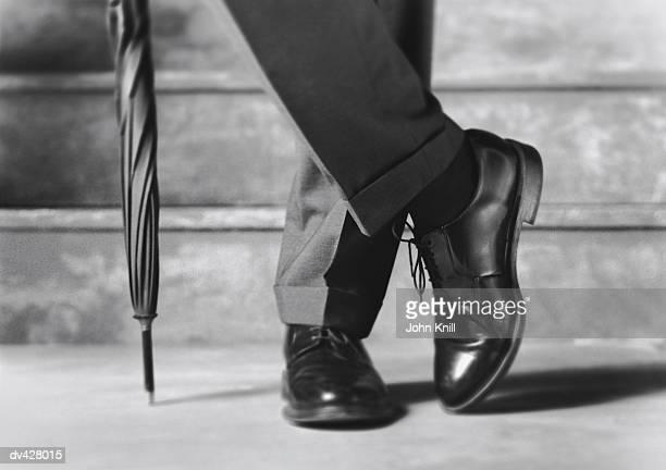 Feet of businessman and umbrella