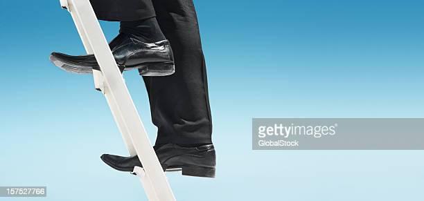 Feet of businessman climbing ladder