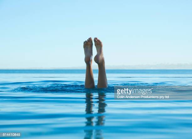 Feet of caucasian girl swimming in tropical ocean