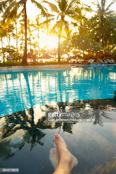 Feet of caucasian man in tropical swimming pool