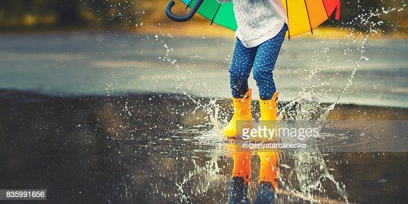 Pies de niño en botas de goma amarillas saltando sobre un charco de lluvia : Foto de stock
