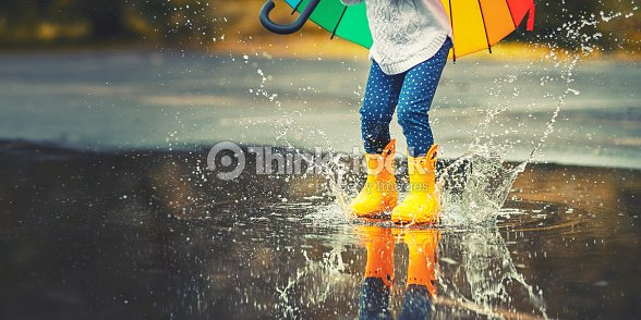 Feet of  child in yellow rubber boots jumping over  puddle in rain : Foto de stock