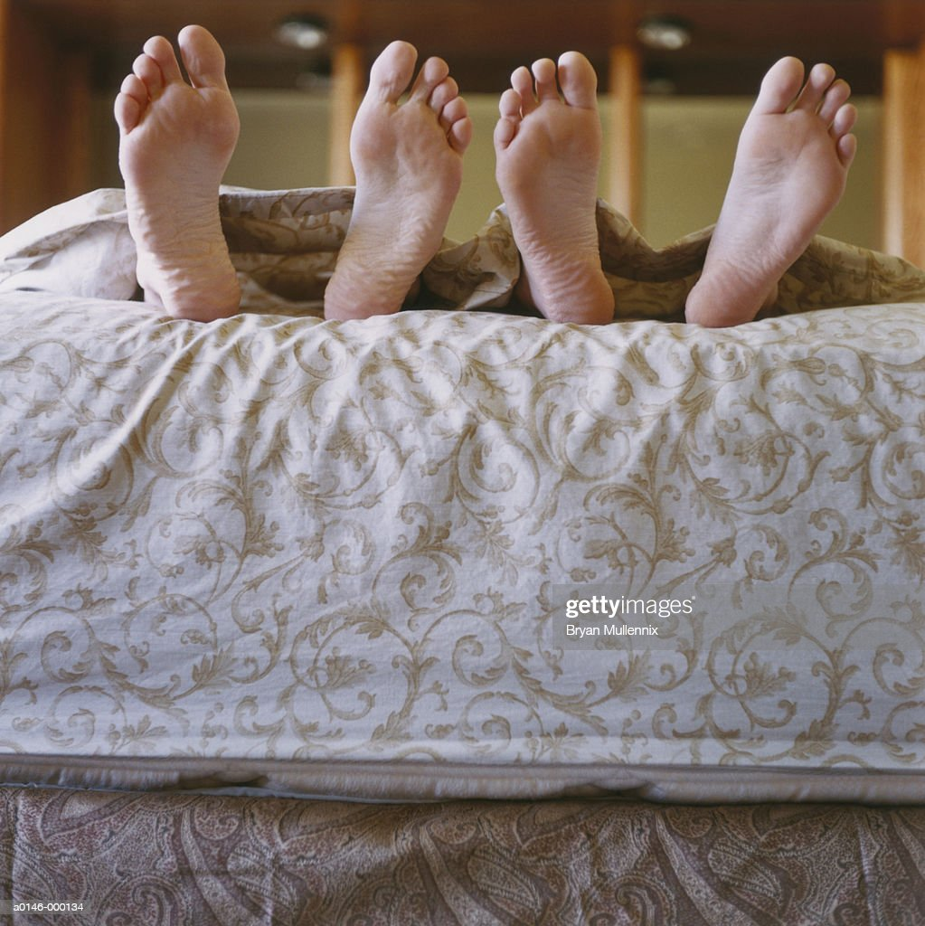 Feet of Couple in Bed : Stock Photo