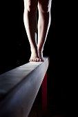 feet of female gymnast on balance beam