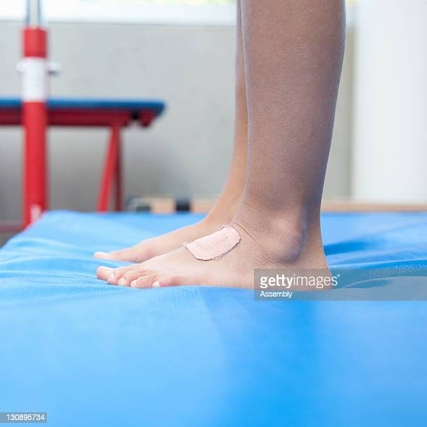 Feet of gymnast on mat, low section