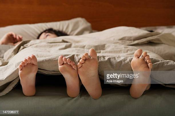 Feet of man and woman in bed