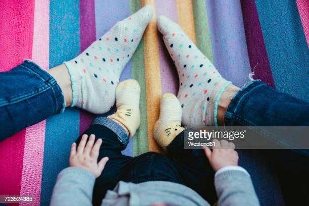 Feet of mother and baby girl on a hammock