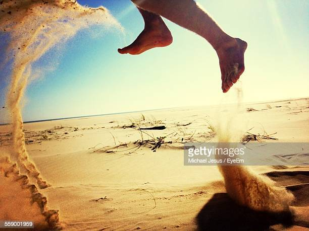 Feet Of Person Jumping On Sandy Beach