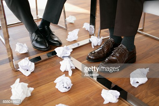 Feet of Two Business Men Under Table and Crumpled Paper on the Floor