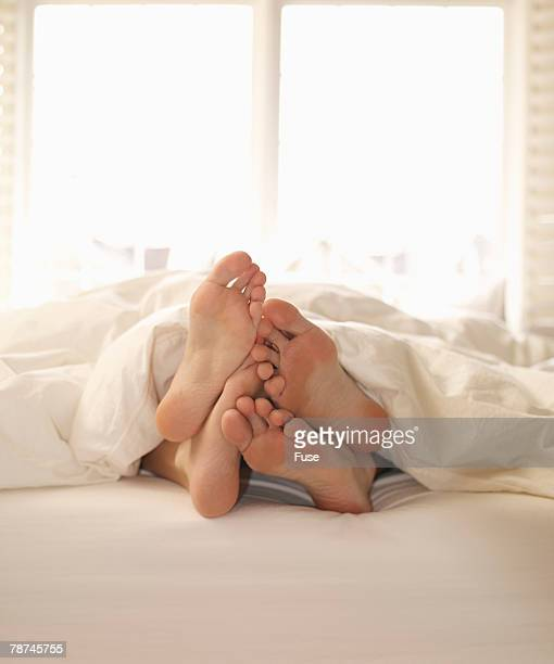 Feet of Two Lovers in Bed