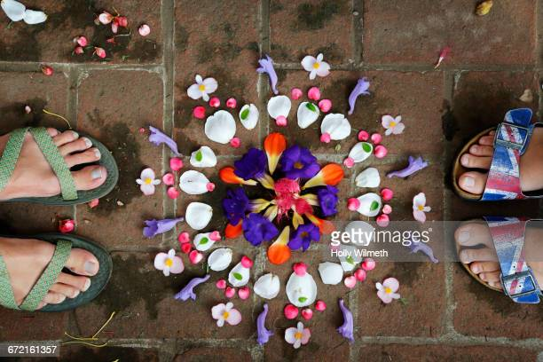 Feet of woman near arranged flowers